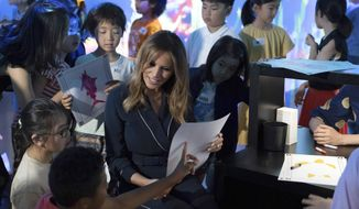 U.S. first lady Melania Trump talks with children during a visit to a digital art museum in Tokyo Sunday, May 26, 2019. (Pierre-Emmanuel Deletree/Pool Photo via AP)