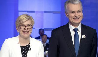 In this photo taken on Wednesday, May 8, 2019, Economist Gitanas Nauseda and Former finance minister Ingrida Simonyte, left, a presidential candidates, pose for the media prior to the start of the televised live debate in Vilnius, Lithuania. Gitanas Nauseda and a former finance minister Ingrida Simonyte held the top two spots in returns from Lithuania's presidential election Sunday, May 26 and appeared headed to a runoff ballot later this month to choose a successor to incumbent Dalia Grybauskaite. (AP Photo/Mindaugas Kulbis)