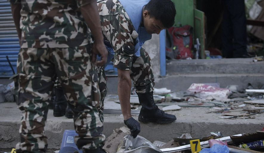 Nepalese army personnel examone the site of an explosion in Kathmandu, Nepal, Sunday, May 26, 2019. Two explosions killed three people and wounded at least five more in different parts of Nepal's capital on Sunday, with police suspecting that an outlawed communist group was responsible. (AP Photo)