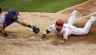 Los Angeles Angels' Kole Calhoun, right, scores on a wild pitch ahead of the tag of Texas Rangers catcher Isiah Kiner-Falefa during the seventh inning of a baseball game Sunday, May 26, 2019, in Anaheim, Calif. (AP Photo/Mark J. Terrill)