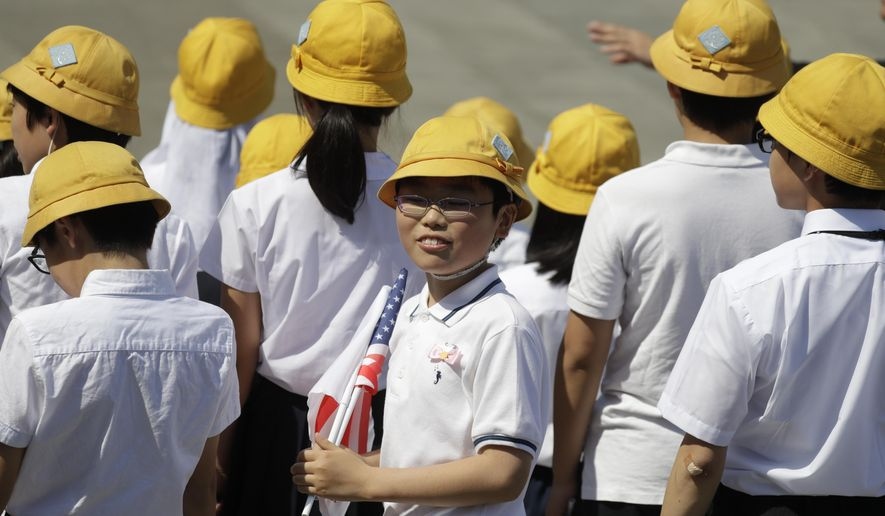 School children wait for President Donald Trump and first lady Melania Trump to arrive participate in a welcome ceremony at the Imperial Palace, Monday, May 27, 2019, in Tokyo. (AP Photo/Evan Vucci)