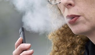 In this April 16, 2019, photo, a woman exhales while vaping from a Juul pen e-cigarette in Vancouver, Wash. (AP Photo/Craig Mitchelldyer) **FILE**