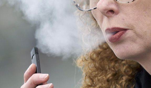 FILE - In this April 16, 2019 file photo, a woman exhales while vaping from a Juul pen e-cigarette in Vancouver, Wash. Schools have been wrestling with how to balance discipline with treatment in their response to the soaring numbers of vaping students. Using e-cigarettes, often called vaping, has now overtaken smoking traditional cigarettes in popularity among students, says the Centers for Disease Control and Prevention. Last year, one in five U.S. high school students reported vaping the previous month, according to a CDC survey. (AP Photo/Craig Mitchelldyer)