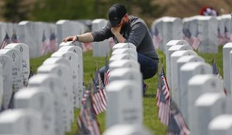 Justin Schor visits the gravestone of his father on Memorial Day at the Great Lakes National Cemetery in Holly, Mich., Monday, May 27, 2019. (AP Photo/Paul Sancya)