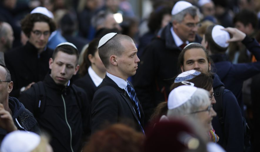 In this Wednesday, April 25, 2018 file photo, people wear Jewish skullcaps, as they attend a demonstration against an anti-Semitic attack in Berlin. Chancellor Angela Merkel's spokesman has stressed Germany's responsibility to ensure security for all Jews wearing skullcaps anywhere in the country without having to fear an anti-Semitic attack. (AP Photo/Markus Schreiber)
