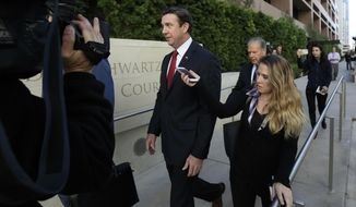 FILE - In this Dec. 3, 2018 file photo Republican Rep. Duncan Hunter, center, leaves court in San Diego. Hunter of has acknowledged taking a photo with a dead combatant during his time as a Marine as he defended a Navy SEAL charged with multiple war crimes. The Republican congressman made the comments during a town hall in his San Diego-area district. (AP Photo/Gregory Bull, File)