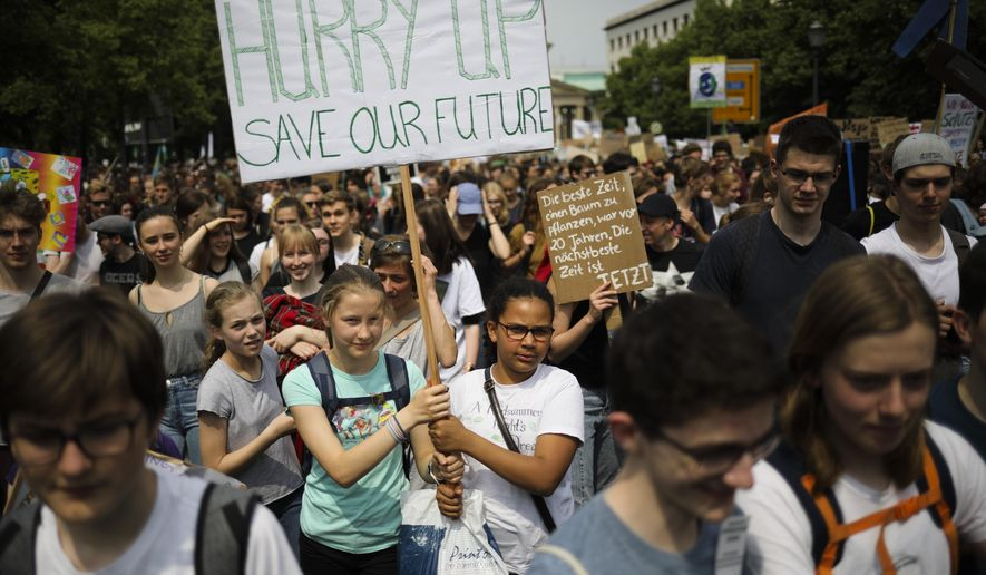 """Students hold posters as they attend a protest rally of the """"Friday For Future"""" movement in Berlin, Germany, Friday, May 24, 2019. The German language poster reads: """"The best time to plant a tree was 20 years ago. The next best time is now."""" (AP Photo/Markus Schreiber) ** FILE **"""