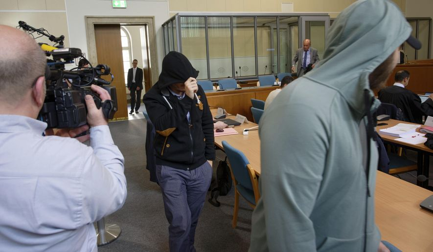 """In this Friday, May 24, 2019, file photo, two defendants of a self-styled """"Sharia police"""" arrive in a courtroom in Wuppertal, Germany. (Henning Kaiser/dpa via AP)"""