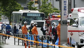 A school bus, center, is parked at the scene of an attack in Kawasaki, near Tokyo Tuesday, May 28, 2019. A man wielding a knife attacked commuters waiting at a bus stop just outside Tokyo during Tuesday morning's rush hour, Japanese authorities and media said. (Kyodo News via AP)