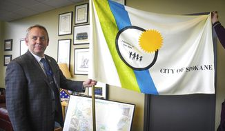 In this Tuesday, May 21, 2019, photo, Spokane Mayor David Condon displays the City of Spokane flag in his office in Spokane, Wash. As the Seattle area becomes more crowded and more expensive, Spokane Mayor David Condon sees an opportunity to grow the state's second-largest city. (Dan Pelle/The Spokesman-Review via AP)