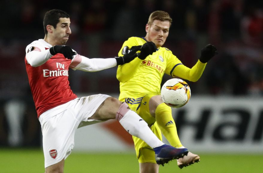 FILE - In this Thursday, Feb. 14, 2019 file photo Arsenal's Henrikh Mkhitaryan, left, duels for the ball with Bate's Aleksandar Filipovic during the Europa League round of 32 first leg soccer match between Bate and Arsenal at the Borisov-Arena in Borisov, Belarus. The choice of Baku as host of the Europa League final provided Arsenal with further grounds for discontent Tuesday when Mkhitaryan, one of the team's most talented players, pulled out of the game for political reasons. (AP Photo/Sergei Grits, File)
