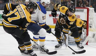 St. Louis Blues' David Perron (57) tries to move the puck between Boston Bruins' Patrice Bergeron (37) and Matt Grzelcyk (48) during the first period in Game 1 of the NHL hockey Stanley Cup Final, Monday, May 27, 2019, in Boston. (AP Photo/Michael Dwyer)