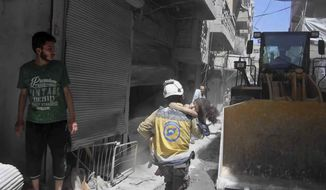 This photo provided by the Syrian Civil Defense White Helmets, which has been authenticated based on its contents and other AP reporting, shows a civil defense worker carrying a child after an airstrike by the Syrian government forces, in the town of Ariha, in the northwestern province of Idlib, Syria, Monday, May 27, 2019. Syria's White Helmets say at least six people were killed and 10 remain under rubble following government air raids on a town in the rebel's last stronghold. (Syrian Civil Defense White Helmets via AP)