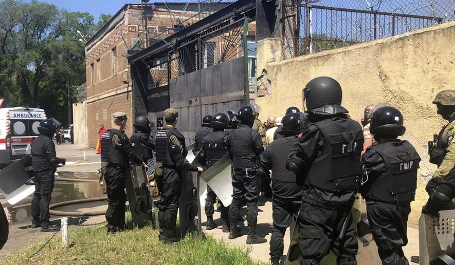In this photo made available by Ukraine's Police Press Service, riot police stand at the prison in Odessa, Ukraine Monday, May 27, 2019. Police says four prison guards have been injured in clashes with inmates who have barricaded themselves in a prison in Ukraine's port city of Odessa. Serhiy Shaykhet, chief of the investigative unit at the Odessa police, said in televised remarks Monday that police are negotiating with the inmates. (Ukrainian Police Press Office via AP)