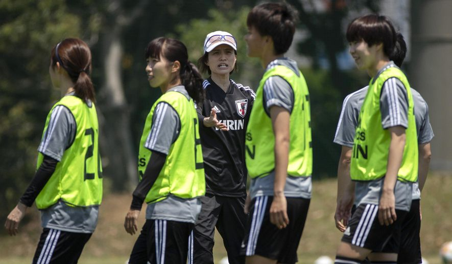 In this Friday, May 24, 2019, photo, Japan women's soccer team head coach Asako Takakura, center, directs her players during a training session in Narashino, east of Tokyo ahead of the FIFA Women's World Cup France. Takakura went to the Women's World Cup twice as a player and is first woman in charge, a fact she largely dismisses. But some see it as a breakthrough in a country that has few women in corporate board rooms or in the top ranks of government. (AP Photo/Jae C. Hong)