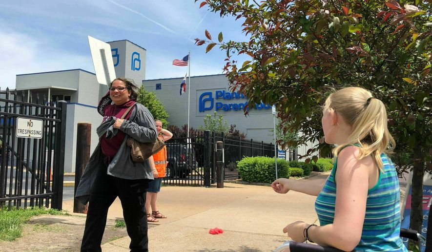 In this May 17, 2019, file photo, Teresa Pettis, right, greets a passerby outside the Planned Parenthood clinic in St. Louis. Pettis was one of a small number of abortion opponents protesting outside the clinic on the day the Missouri Legislature passed a sweeping measure banning abortions at eight weeks of pregnancy. Planned Parenthood says Missouri's only abortion clinic could be closed by the end of the week because the state is threatening to not renew its license, which expires Friday, May 31. (AP Photo/Jim Salter, File)