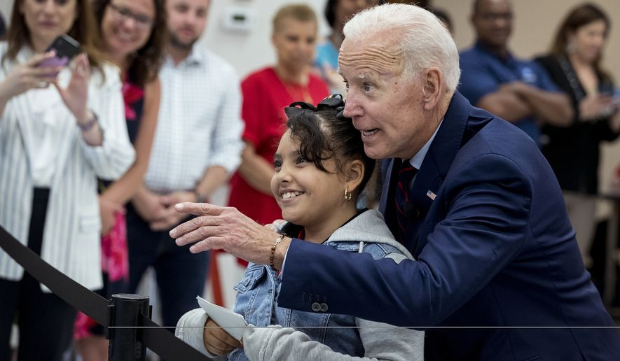 Former Vice President Joe Biden, a 2020 Democratic presidential hopeful, takes Virmania Villalobos, 10, back to introduce her to members of the media after she asked him a question during a town all meeting with a group of educators from the American Federation of Teachers on Tuesday, May 28, 2019, in Houston. Biden asked her what her favorite subject in school was and she responded: journalism. Which prompted Biden to walk her back to the media riser. (Brett Coomer/Houston Chronicle via AP)
