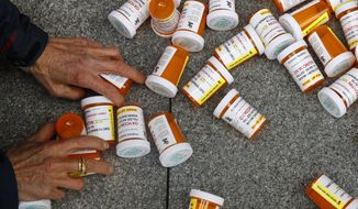 FILE - In this Friday, April 5, 2019, file photo, a protester gathers containers that look like OxyContin bottles at an anti-opioid demonstration in front of the U.S. Department of Health and Human Services headquarters in Washington, D.C. The U.S. has backed away from recommending opioids for long-term treatment of chronic pain. Nevertheless, companies continue pushing the drugs in other countries, and consumption is growing. Researchers in Brazil report, for example, that prescription opioid sales have increased 465 percent in six years. (AP Photo/Patrick Semansky)