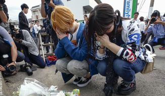 """Women pray after offering flowers near the scene where a man wielding a knife attacked commuters in Kawasaki, near Tokyo Tuesday, May 28, 2019. A man carrying a knife in each hand and screaming """"I will kill you!"""" attacked a group of schoolgirls and adults as he walked toward a bus stop just outside Tokyo on Tuesday, officials said(Kyodo News via AP)"""