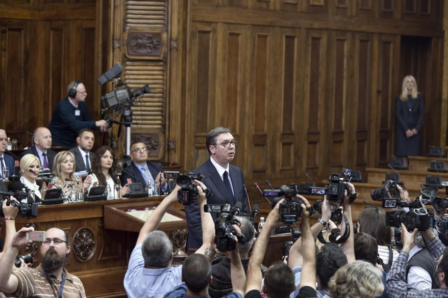 Aleksandar Vucic, the president of Serbia, center, prepares to speak during a session of Serbia's parliament in Belgrade, Serbia, Monday, May 27, 2019. Vucic addressed the Serb parlamentarians during a session devoted to the situation in Kosovo, which declared independence from Serbia in 2008. (AP Photo/Marko Drobnjakovic)