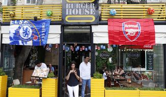 A restaurant is decorated with Chelsea and Arsenal flags, in central Baku, Azerbaijan Tuesday, May 28, 2019. Supporters were arriving in the Azerbaijan capital ahead of Wednesday's Europa League final between English teams Arsenal and Chelsea. (AP Photo/Darko Bandic)