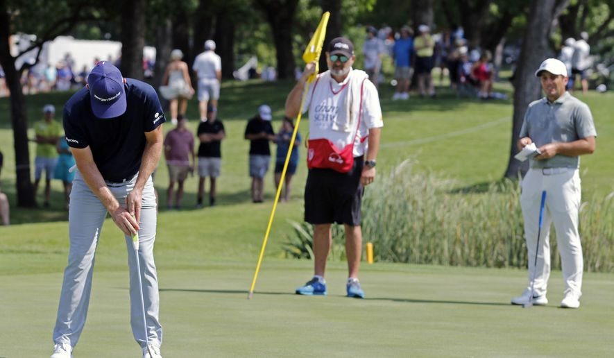 Justin Rose putts on the ninth green, with caddie Mark Fulcher and Francesco Molinari in the background, during the third round of the Charles Schwab Challenge golf tournament at Colonial Country Club in Fort Worth, Texas, Saturday, May 25, 2019. (Bob Booth/Star-Telegram via AP)