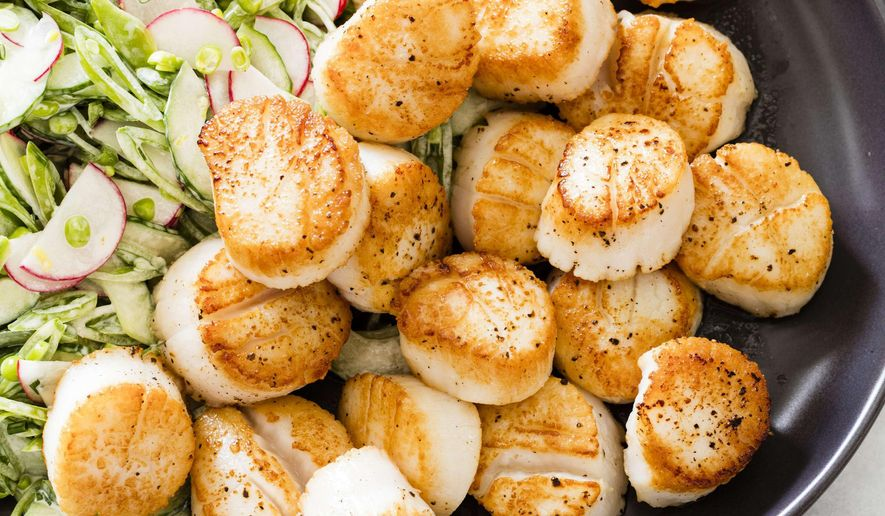"""This undated photo provided by America's Test Kitchen in May 2019 shows Pan-Seared Scallops with Slaw  in Brookline, Mass. This recipe appears in the cookbook """"Vegetables Illustrated."""" (Daniel J. van Ackere/America's Test Kitchen via AP)"""