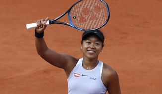 Japan's Naomi Osaka celebrates winning her first round match of the French Open tennis tournament against Slovakia's Anna Karolina Schmiedlova in three sets, 0-6, 7-6 (7-4), 6-1, at the Roland Garros stadium in Paris, Tuesday, May 28, 2019. (AP Photo/Christophe Ena )