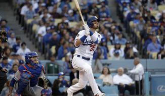 Los Angeles Dodgers' Cody Bellinger, right, follows through on a solo home run against the New York Mets during the third inning of a baseball game Monday, May 27, 2019, in Los Angeles. (AP Photo/Marcio Jose Sanchez)