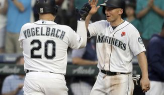 Seattle Mariners' Daniel Vogelbach (20) is greeted at the dugout by Kyle Seager after Vogelbach hit a two-run home run against the Texas Rangers during the seventh inning of a baseball game, Monday, May 27, 2019, in Seattle. (AP Photo/Ted S. Warren)