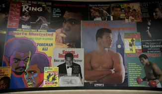 """In this June 4, 2016, file photo large posters of mostly Sports Illustrated magazine covers are displayed at the """"I Am The Greatest, Muhammad Ali"""" exhibition at the O2 arena, which hosts high profile boxing fights in London. Sports Illustrated is being sold for $110 million, but the seller will continue running the iconic magazine under a licensing deal. Authentic Brands Group is buying Sports Illustrated from Meredith Corp. (AP Photo/Matt Dunham, File)"""