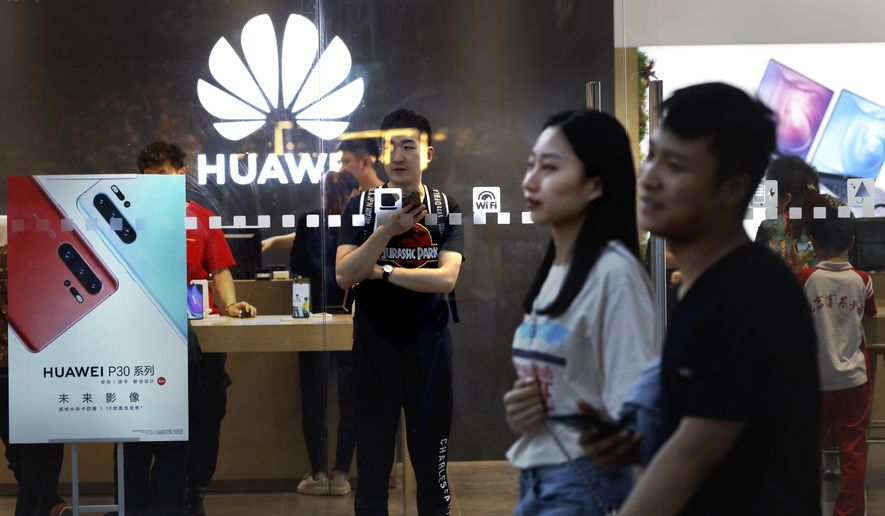 In this Monday, May 20, 2019, file photo, shoppers visit a Huawei store in Beijing. Chinese tech giant Huawei has filed a motion in U.S. court challenging the constitutionality of a law that limits its sales of telecom equipment. (AP Photo/Ng Han Guan)