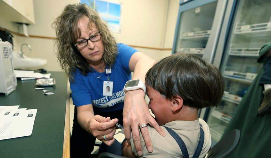 In this Friday, May 17, 2019, file photo, Starr Roden, left, a registered nurse and immunization outreach coordinator with the Knox County Health Department, administers a vaccination to Jonathan Detweiler, 6, at the facility in Mount Vernon, Ohio. (AP Photo/Paul Vernon)