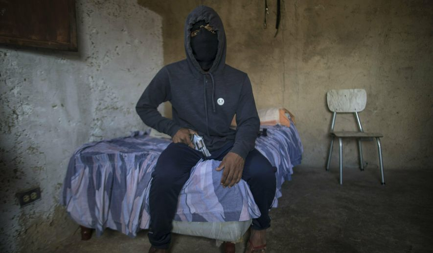 """A masked gangster who goes by the nickname """"El Negrito"""" poses for a portrait with his gun inside his gang's safe-house in the Petare slum of Caracas, Venezuela, Monday, May 13, 2019. The 24-year-old, who says he's lost track of his murder count, is quick to gripe about how Venezuela's failing economy is cutting into his profits and has considered leaving the trade in Venezuela and emigrating. (AP Photo/Rodrigo Abd)"""