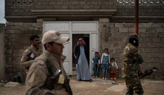 In this April 5, 2019, photo, residents watch as local militia and Iraqi army soldiers walk past their home during a raid in Badoush, Iraq. (AP Photo/Felipe Dana) ** FILE **