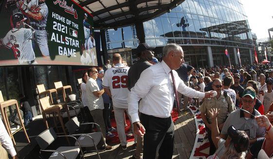 In this file photo from May. MLB Commissioner Rob Manfred signs baseballs for fans in Atlanta. (AP Photo/John Bazemore)