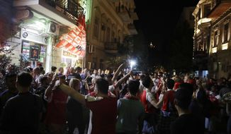 Arsenal supporters stand outside a pub in Baku, Azerbaijan, Tuesday May 28, 2019. English Premier League teams Arsenal and Chelsea are preparing for the Europa League Final soccer match that takes place in Baku on Wednesday night. (AP Photo/ Luca Bruno)
