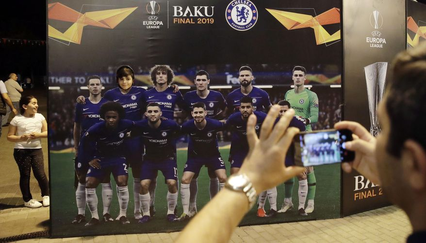 Tourists take pictures in at the fan zone in Baku, Azerbaijan, Tuesday May 28, 2019. English Premier League teams Arsenal and Chelsea are preparing for the Europa League Final soccer match that takes place in Baku on Wednesday night. (AP Photo/ Luca Bruno)