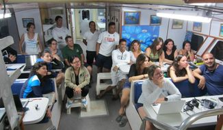 In this Dec. 12, 2018 photo provided by the Environmental Defense Fund, Patricia Gonzalez, director of the University of Havana's Center for Marine Research, third from right, sitting in front of a laptop, attends a field workshop with fellow Cuban scientists, and government officials, aboard a vessel at Parque Nacional Jardines de la Reina, Cuba. The New York-based Environmental Defense Fund has worked with Cuban universities, research centers and the Cuban government for 19 years on marine and coastal conservation. (Environmental Defense Fund via AP)