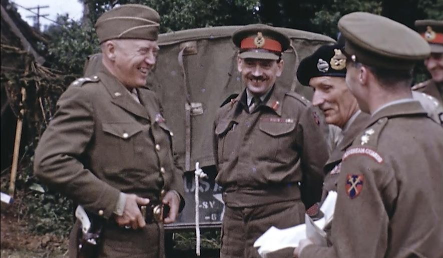 Gen. George Patton, with a pearl-handled pistol, talks to French officers in France during World War II. Seventy-five years later, surprising color images of the D-Day invasion and aftermath bring an immediacy to wartime memories. They were filmed by Hollywood director George Stevens and rediscovered years after his death.  (War Footage From the George Stevens Collection at the Library of Congress via AP)