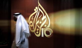 In this Nov. 1, 2006 file photo, a Qatari employee of Al-Jazeera Arabic language TV news channel walks past the logo of Al-Jazeera in Doha, Qatar. (AP Photo/Kamran Jebreili, File) ** FILE **