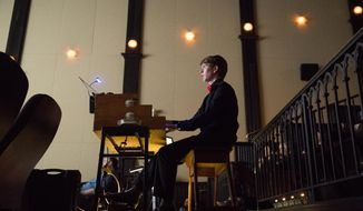 """In this April 24, 2019 photo, Brett Miller plays in the glow of the movie screen at Princeton Garden Theatre  in Princeton, N.J., to the silent films """"Trip to the Moon"""" and """"The Black Pirate."""" The 16-year-old has a passion for a lost art: playing live organ accompaniment to silent films. (Charles Fox/The Philadelphia Inquirer via AP)"""