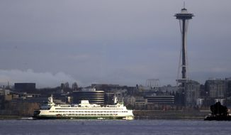 FILE - In this Dec. 27, 2018, file photo, a Washington State ferry heading into Elliott Bay is illuminated by the sun as the city behind remains under clouds in Seattle.. Authorities say a Washington State ferry struck a whale Tuesday night, May 28, 2019, during a sailing from Seattle to Bainbridge Island. (AP Photo/Elaine Thompson,File)