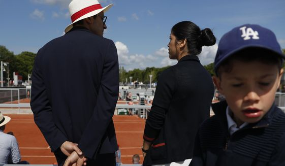 A host and hostess wait for spectators to arrive to watch second round matches of the French Open tennis tournament at the Roland Garros stadium in Paris, Wednesday, May 29, 2019. (AP Photo/Pavel Golovkin)