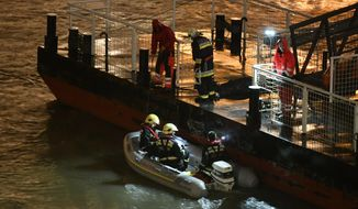 Responders sit in a rubber dinghy preparing for the search of victims next to a landing dock after a tourist boat crashed with another ship late Wednesday, May 29, 2019. The boat capsized and sunk in the Danube River Wednesday evening, May 29, 2019, in Budapest, with dozens of people on board, including passengers and crew, Hungarian media reported. (Zsolt Szigetvary/MTI via AP)
