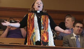 Rev. Sarah Ogelsby-Dunegan, a Unitarian minister from Topeka, Kan., leads a protest in favor of Medicaid expansion, Wednesday, May 29, 2019, in the Senate gallery at the Statehouse in Topeka, Kan. The protest temporarily shut down the Senate, and nine protesters were arrested. (AP Photo/John Hanna)