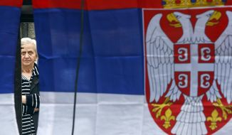 A Kosovo Serb woman is framed by Serbian flags as she attends a protest against Kosovo police action in the northern Serb-dominated part of ethnically divided town of Mitrovica, Kosovo, Wednesday, May 29, 2019. Russia and Serbia have blamed NATO and the West for an armed raid by Kosovo police in the Serb dominated north of Kosovo when a Russian U.N. employee was among more than two dozen people arrested in what Kosovo says was an anti-organized crime operation. (AP Photo/Visar Kryeziu)