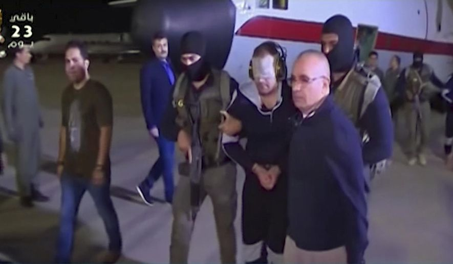 In this frame grab from Egyptian State Television, a blindfolded Hisham el-Ashmawi, a prominent Egyptian militant is escorted by Egyptian military officers and placed in a vehicle after being taken off a military plane at an airport in Cairo, Egypt, Wednesday, May 29, 2019. El-Ashmawi was captured last October in the Libyan city of Derna, a longtime bastion of Islamic militants, by commander Khalifa Hifter's self-styled Libyan National Army. (Egyptian State Television via AP)