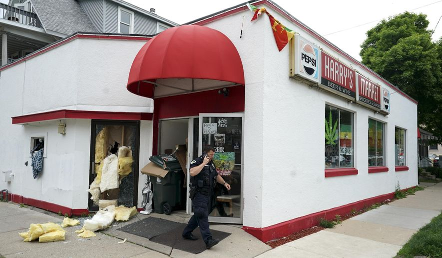 A police officer walks in front of the Lion of Judah House of Rastafari church in Wednesday May 29, 2019, in Madison, Wis. Several suspects were arrested because the self-styled church was distributing marijuana to its members for donations. Madison police said the raid on the storefront church was initiated by the Dane County Narcotics Task Force. (Steve Apps/Wisconsin State Journal via AP)