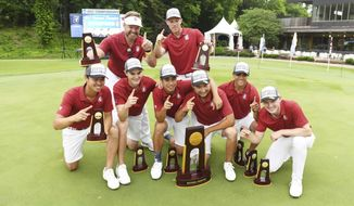 The Stanford mens golf team celebrates with their national championship trophy after the final round against Texas in the NCAA men's college golf tournament Wednesday, May 29, 2019, in Fayetteville, Ark. (AP Photo/Michael Woods)